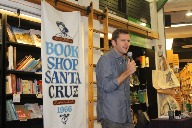 Chris Guillebeau addresses crowd at author event.